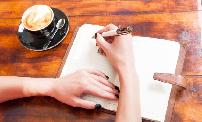Woman hands writing on notebook on terrace