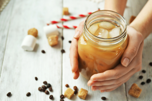 Woman holding iced coffee drink on wooden background