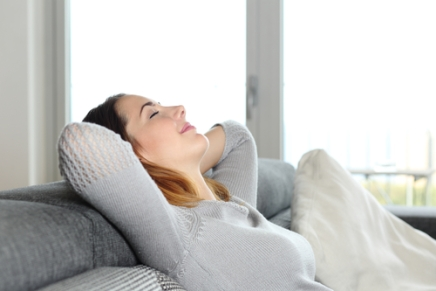 Happy relaxed woman resting on a couch at home