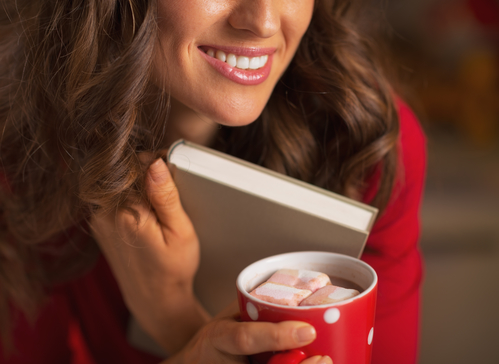 Closeup on young woman with christmas cup of hot chocolate with marshmallow hugging book