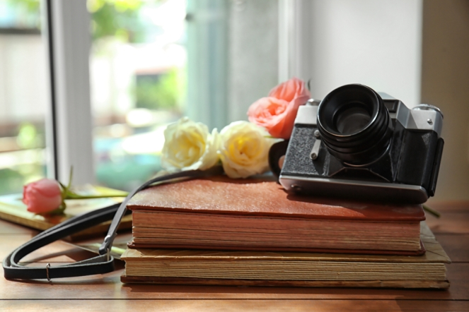 Vintage camera and beautiful roses on photo albums
