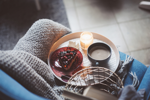 Cozy winter weekend at home. Morning with coffee or cocoa, berry pie, books, warm knitted blanket and nordic style chair. Hygge concept.
